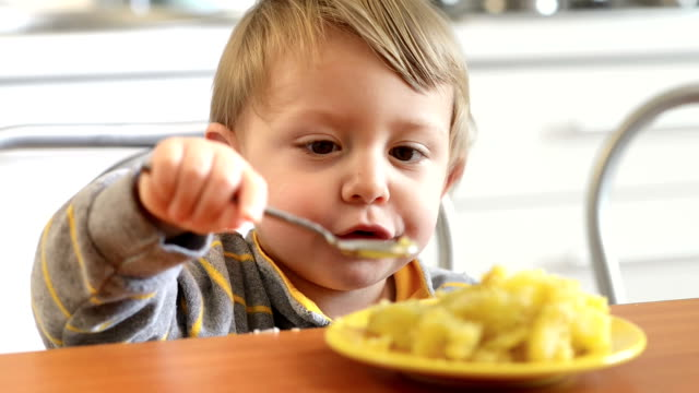 Little Boy Eating Potatoes Cute little boy eating and smiling in the kitchen hungry child stock videos & royalty-free footage