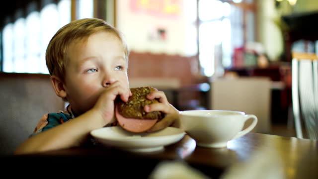 Little boy eating sandwich in a cafe video