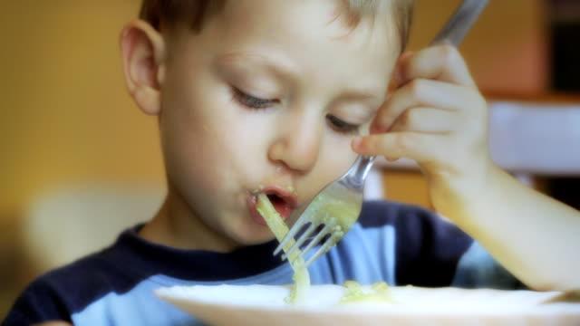 Little boy eating spaghetti. video