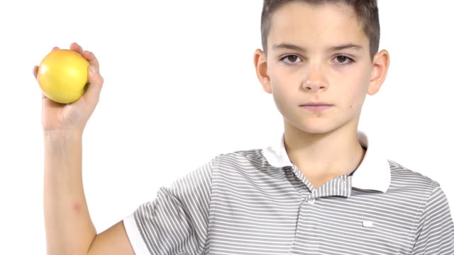 Little boy eats apple at white background video