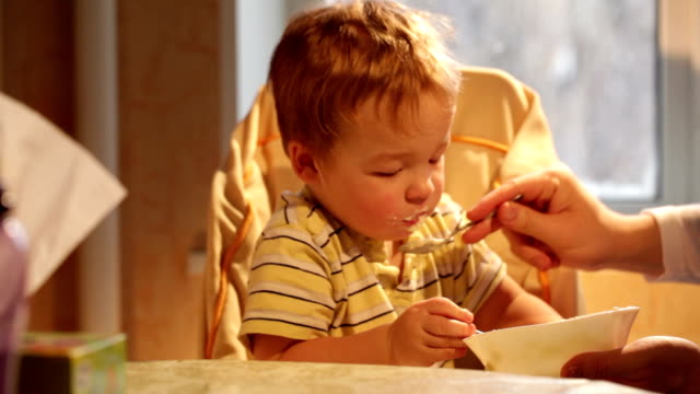 Little boy eats porridge. video