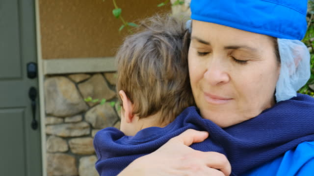 kleiner junge umarmt seine mutter, die eine gesundheitshelferin ist und er sah wochenlang nicht, weil sie damit beschäftigt war, menschen zu heilen, weil covid-19 - held stock-videos und b-roll-filmmaterial