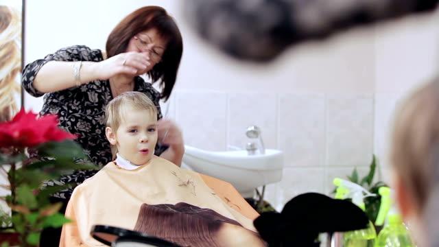 ragazzino gode processo di taglio di capelli. - bassino video stock e b–roll