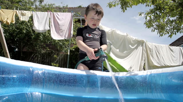 Little Boy Filling Up An Inflatable Wading Pool Slow Motion video