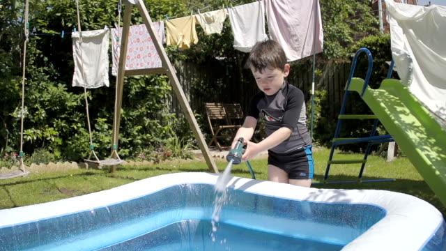 piccolo ragazzo che riempie un gonfiabile piscina per bambini rallentatore - tubo flessibile video stock e b–roll
