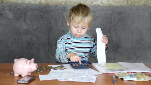 vidéos et rushes de petit garçon financier - tirelire