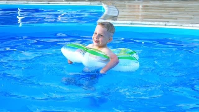 liten pojke flyta på uppblåsbara cirkel i blå poolen. - inflatable ring bildbanksvideor och videomaterial från bakom kulisserna