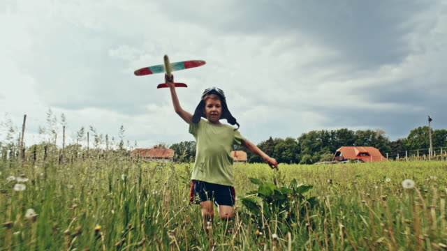 SLO MO Little boy flying airplane across the grass
