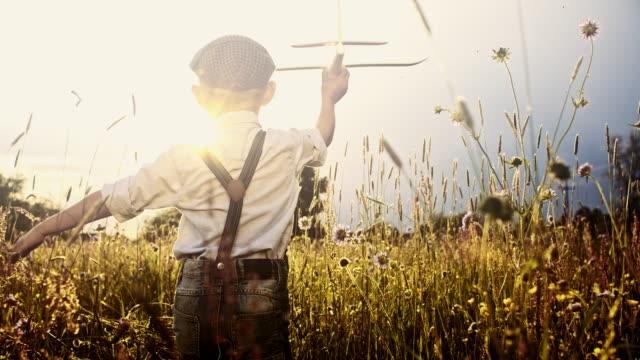 slo mo kleiner junge fliegen flugzeug während des durchlaufs durch wiese - träumen stock-videos und b-roll-filmmaterial
