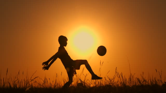 vídeos de stock e filmes b-roll de little boy football player silhouette, practicing with the ball, the sunset golden hour, slow motion. - chutar