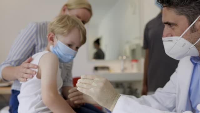 vídeos y material grabado en eventos de stock de niño recibiendo una inyección de gripe de pediatra - flu shot