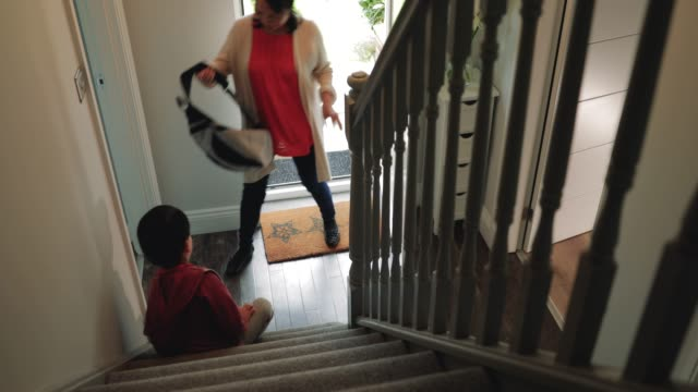 little boy getting help to remove his shoes - rimuovere video stock e b–roll