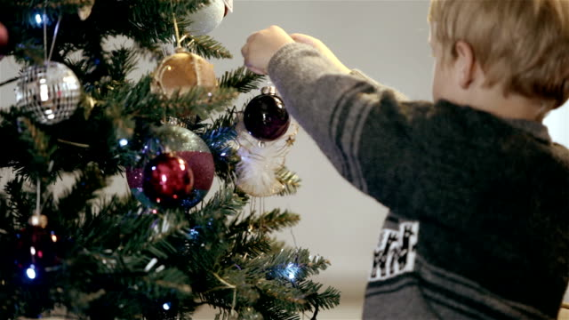 Little boy hangs bauble on christmas tree A tight shot of a single little boy hanging a bauble onto a Christmas tree. hanging stock videos & royalty-free footage