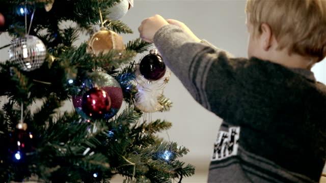 stockvideo's en b-roll-footage met little boy hangs bauble on christmas tree - hangen