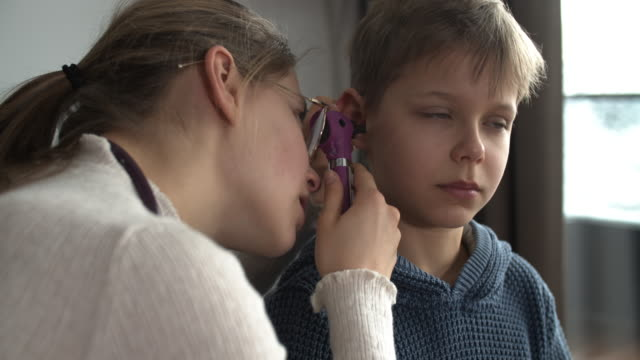 little boy having an ear examination - orecchio umano video stock e b–roll