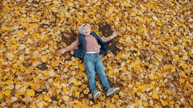 little boy having fun while making leaf angels - angelo video stock e b–roll