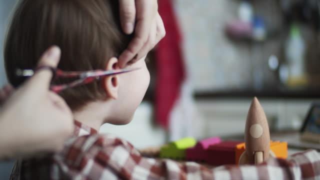 vídeos de stock e filmes b-roll de little boy having his hair cut at home during quarantine - covid hair