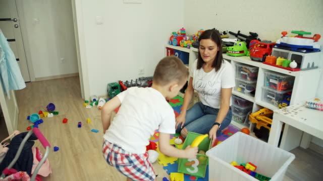 小さな男の子は、おもちゃから部屋をきれいに母を助ける - 楽しい 洗濯点の映像素材/bロール