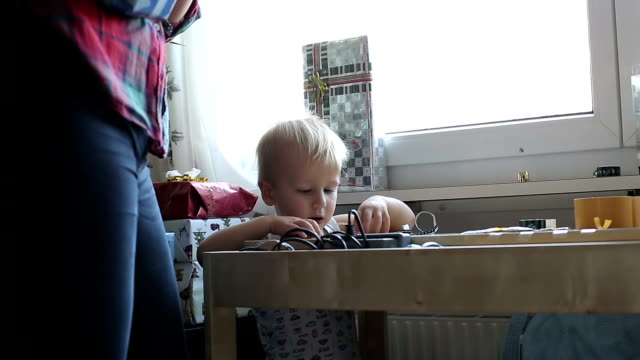 Little boy helps mother to decorate gift boxes. video