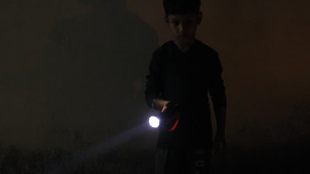 little boy holding a pocket torch light and searching in the darkness. little boy holding a pocket torch light and searching in the darkness. flashlight stock videos & royalty-free footage