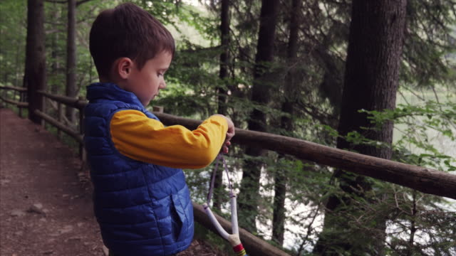 Little boy holding sling with stone video
