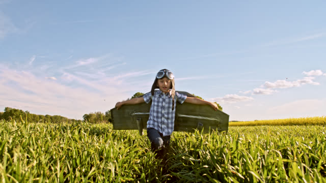 SLO MO Little boy in a jet pack costume running in a wheat field video