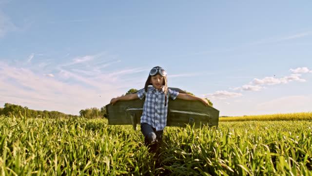 slo mo liten pojke i en jet pack kostym körs i en veteåker - föreställningsförmåga bildbanksvideor och videomaterial från bakom kulisserna