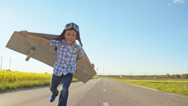 SLO MO Little boy in a jet pack costume running toward camera Slow motion front view shot of a little boy in a retro airplane costume running toward camera on a country road. Slovenia one boy only stock videos & royalty-free footage