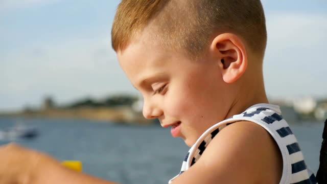 少年は海を前に双眼鏡のペアを保持しているストライプのシャツ - 4歳から5歳点の映像素材/bロール