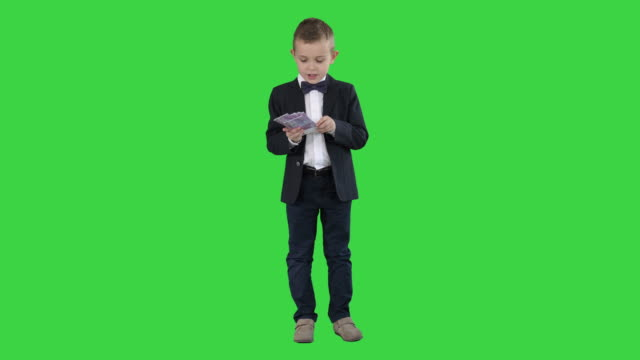 Little boy in a suit counting money on a Green Screen, Chroma Key