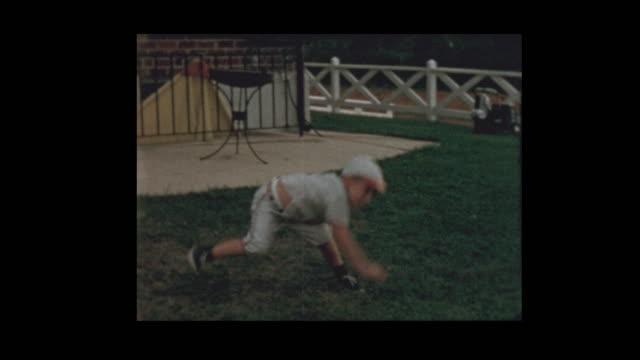 1956 Little boy in baseball uniform plays catch with dad