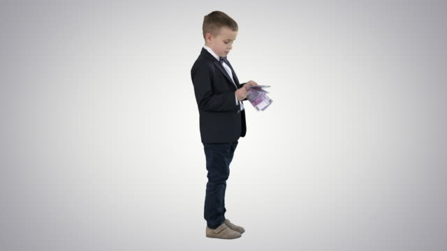 little boy in black suit counts money on gradient background - salvadanaio video stock e b–roll
