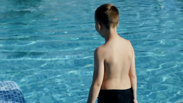 little boy in black swimming trunks jumps into the blue pool - solo un bambino maschio video stock e b–roll