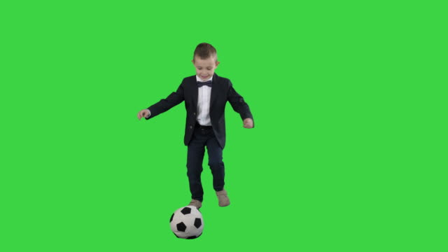 vídeos de stock e filmes b-roll de little boy in costume shooting at goal on a green screen, chroma key - campeão soccer football azul