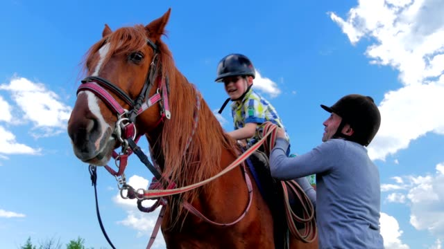Little boy in helmet sitting on the horse and waving hand video