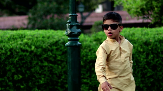 Little boy in sunglasses and having fun dancing in summer park 4K Video : Cute innocent little Indian boy dancing outdoors in the nature. one boy only stock videos & royalty-free footage