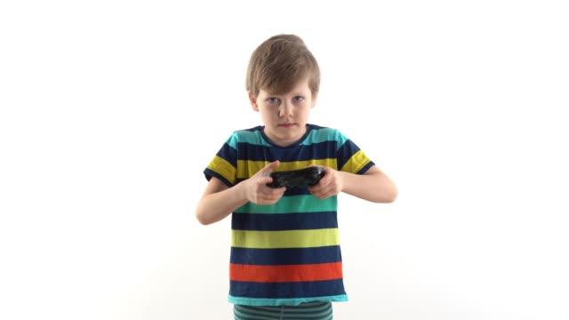 stockvideo's en b-roll-footage met weinig jongen in de studio op een witte achtergrond speelt de joystick in videospelletjes - kids online abuse