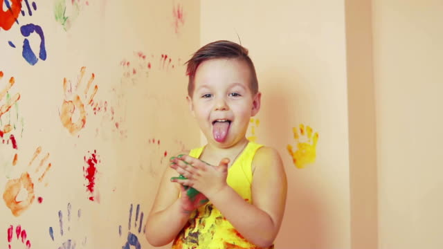little boy in yellow sleeveless shirt showing tongue. his hands are dirty in colors. he is living his handprints on the wall. slowmotion - birichinata video stock e b–roll
