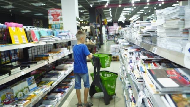 vidéos et rushes de petit garçon est l'achat d'articles de papeterie pour l'école. - fournitures scolaires