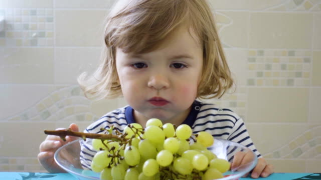 Little boy is eating grapes from a plate sitting at a table.