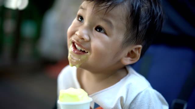 vídeos de stock e filmes b-roll de little boy is eating ice cream. - boca suja