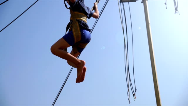 a little boy is jumping on rubber ropes in an amusement park. it is sunny summer. the strong sun is shining. the boy is happy. - bungee jumping video stock e b–roll