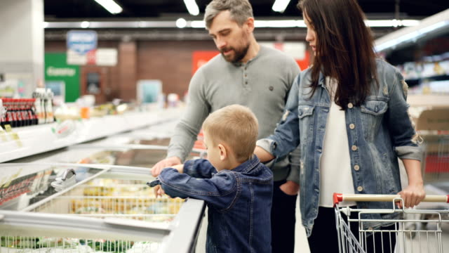little boy is opening freezer and taking pack of frozen vegetables then giving it to his daddy while shopping in supermarket with his family. people and shop concept. - замороженные продукты стоковые видео и кадры b-roll