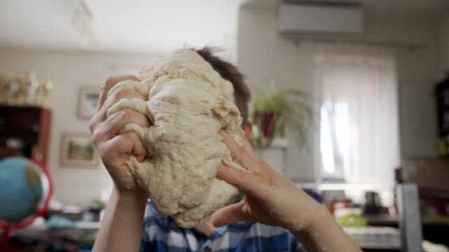 vídeos de stock e filmes b-roll de little boy is playing with the dough he is kneading - baking bread at home