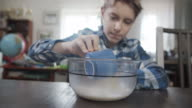 istock Little boy is pouring a cup of melted butter to the bowl 1215701140