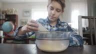 istock Little boy is pouring dried yeast to the bowl 1215703632