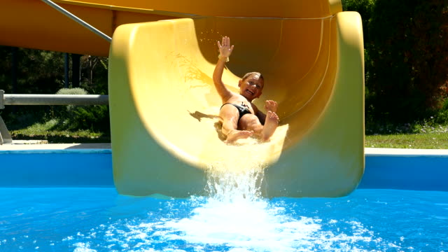 little boy is riding a water slide in an aquapark video