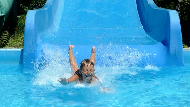 little boy is riding a water slide (slow motion) - scivolo video stock e b–roll