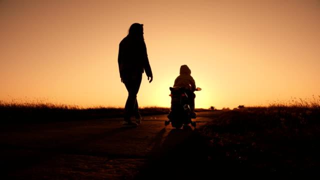 vidéos et rushes de petit garçon est monté sur un jouet moto électrique - moto sport