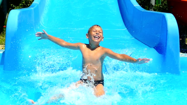 little boy is riding on the water slides of the water park (slow motion) video